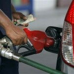 An employee fills a vehicle with petrol at a fuel station in New Delhi