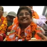 Kiran Bedi, garlanded, in open truck for road show